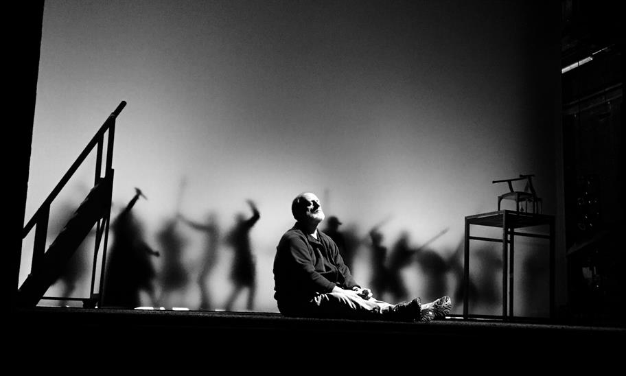 Black and white photo of David Troughton sitting on the stage as Gloucester with silhouetted figures in the background
