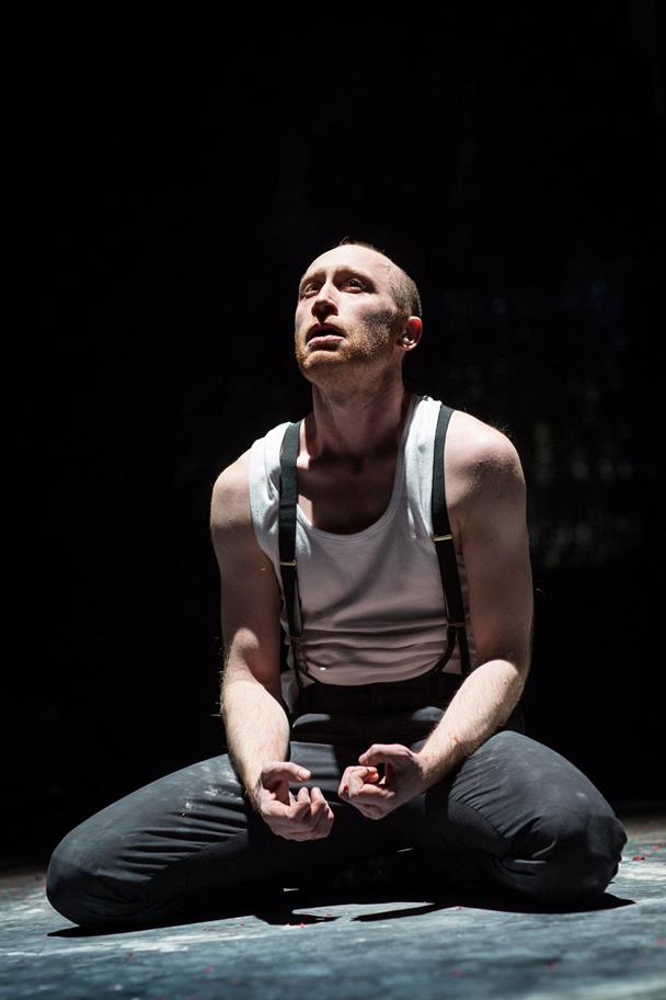 Doctor Faustus in a white vest and suspenders, kneeling on the floor and looking up into the light