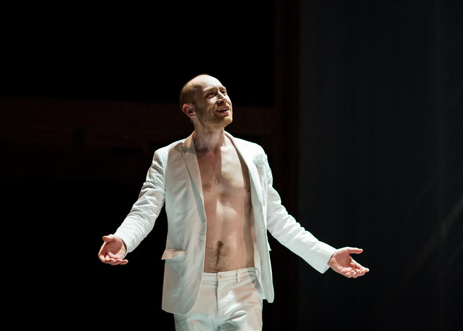 Mephistophilis wearing a white jacket and white trousers, bare-chested, spreads out his hands