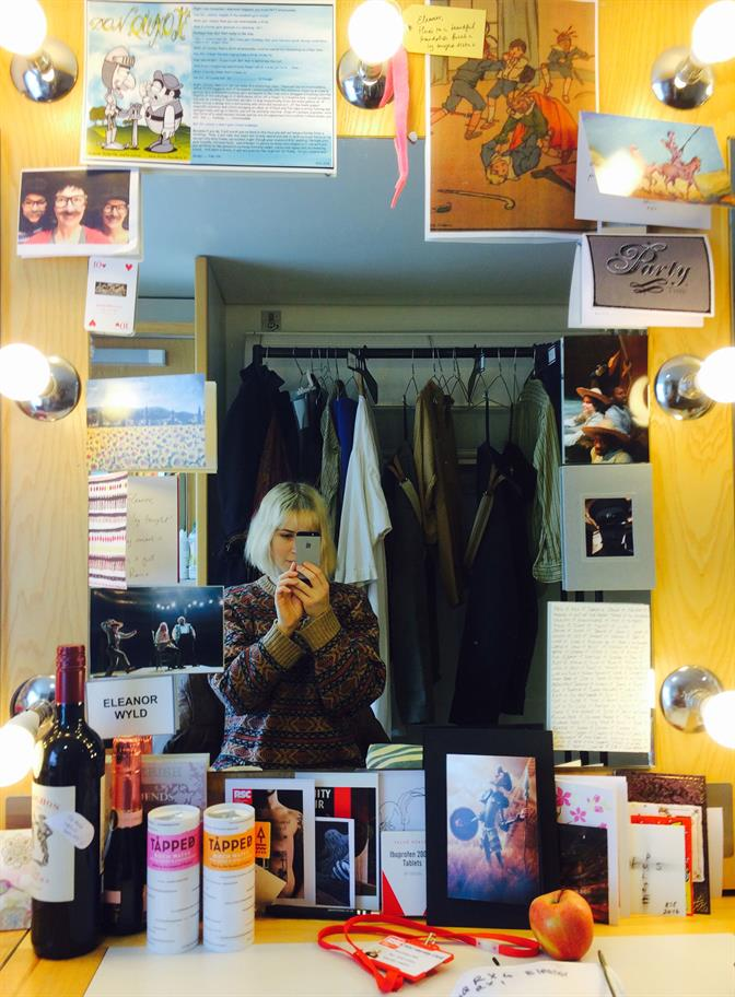 Selfie of Eleanor taken in her dressing room mirror, showing card around her mirror, an apple, a bottle of wine and 2 bottles of birch water