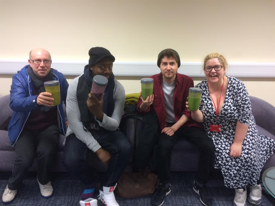 Four people sit on a sofa carrying brightly coloured smoothies