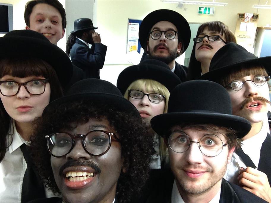 The cast of Doctor Faustus all dressed in white shirts, with black jackets, black hats and glasses