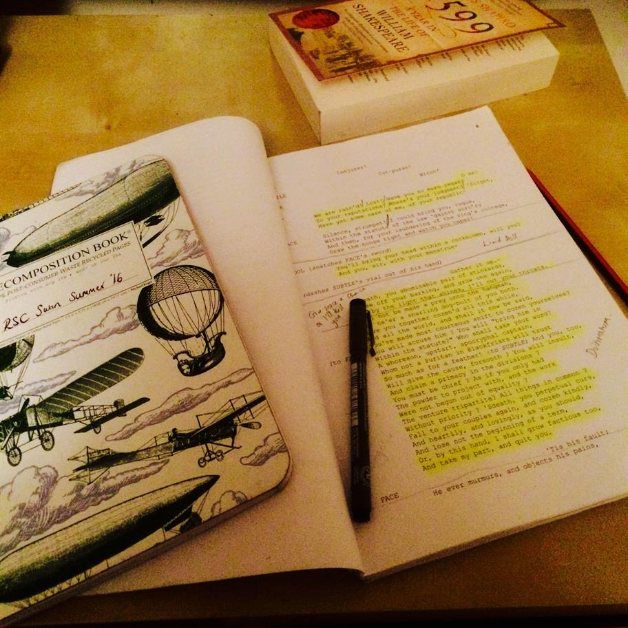 A notebook and a script on the table, the page open in the script is heavily highlighted