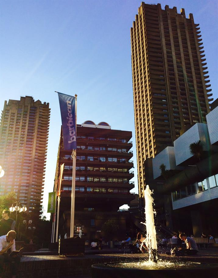 A blue Barbican flag next to a fountain among three tall buildings