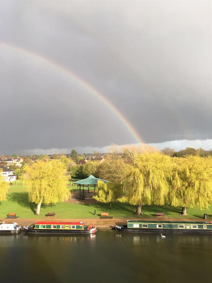 A rainbow over the river Avon under a grey sky