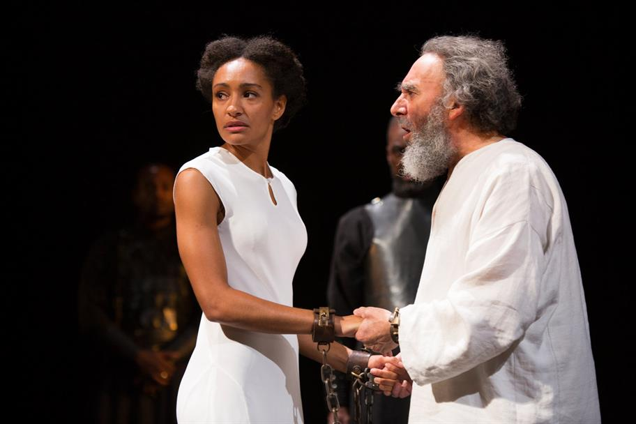 Natalie Simpson as Cordelia, wearing a white dress and shackles, with Antony Sher as King lear, wearing a white robe and shackles