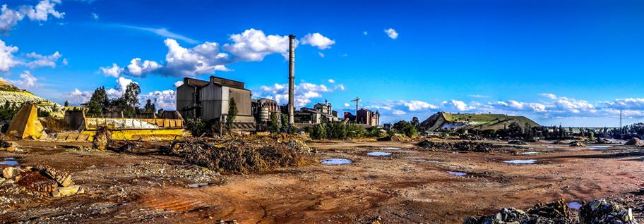 The area around Randfontein mine - a buidlign with a mineshaft and mud and puddles, filtered to look like a painting