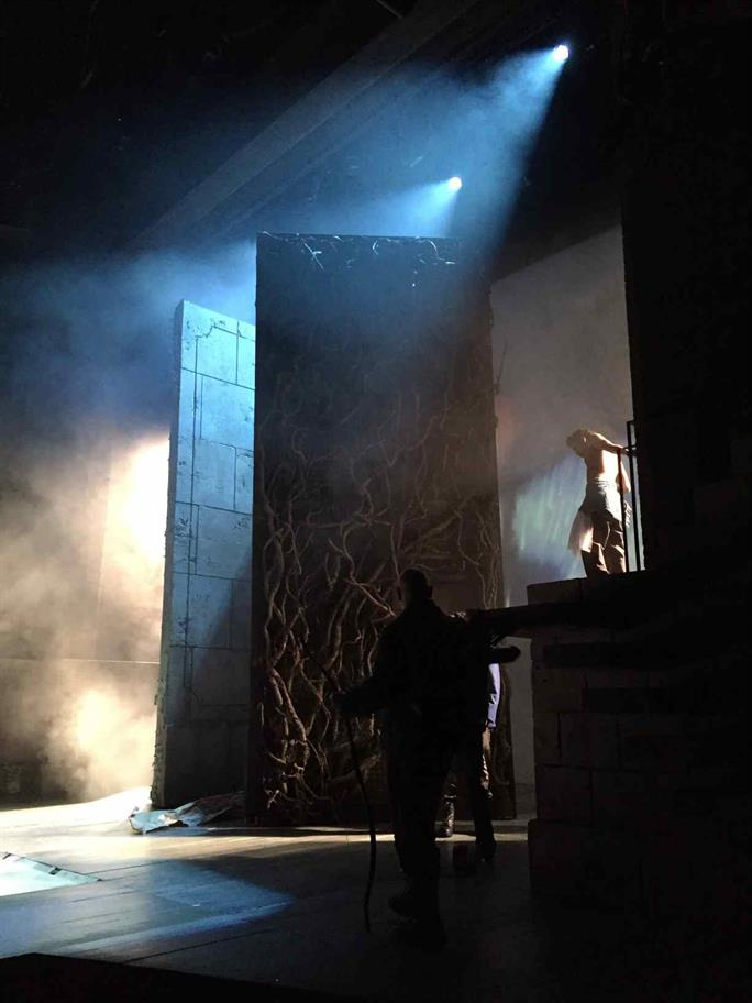 The stage for Cymbeline with two tall towers, blue lights and smoke