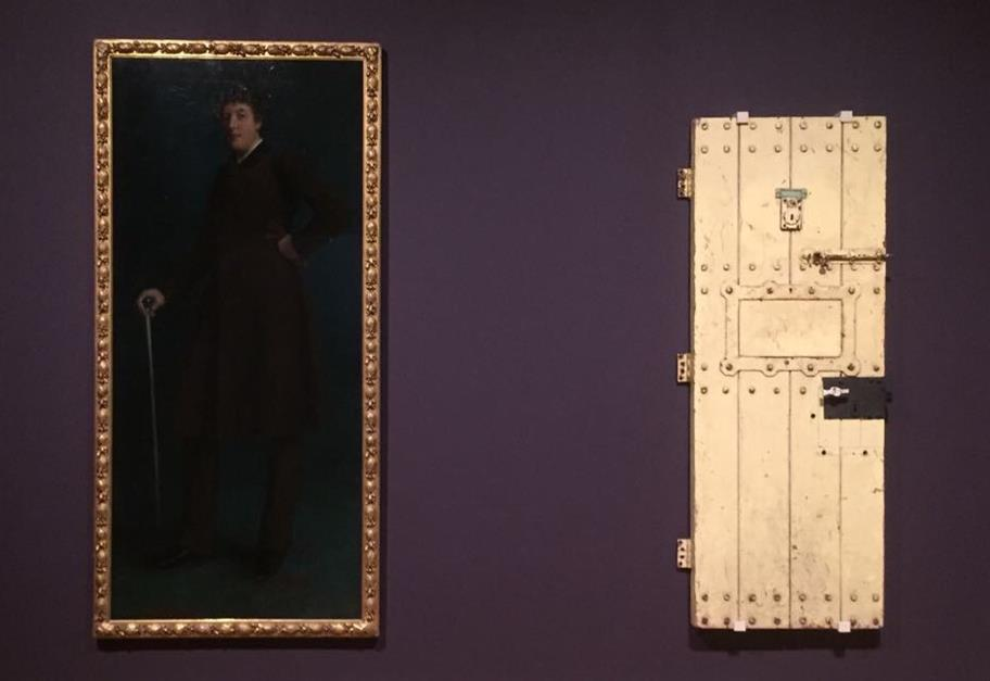 A portrait of Oscar Wilde (left) hanging on a purple wall next to a cell door (right)