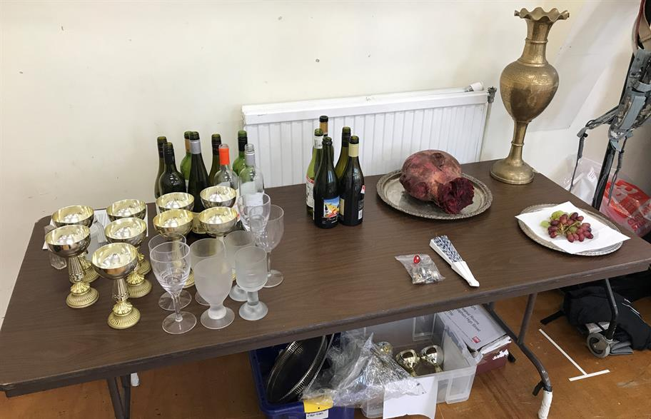 A table covered in props for Salome - mostly wine bottles and glasses