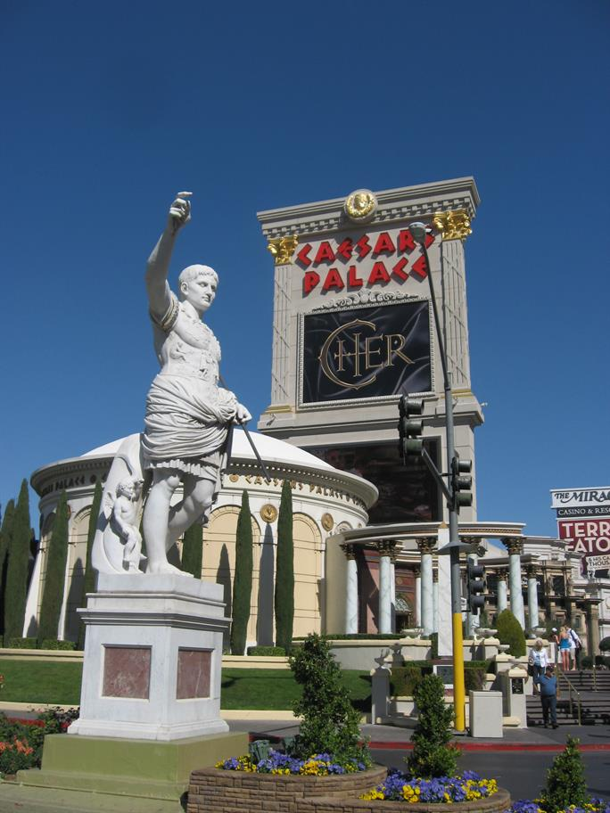 A statue of Caesar with his arm out and a sign behind which reads Caesars Palace