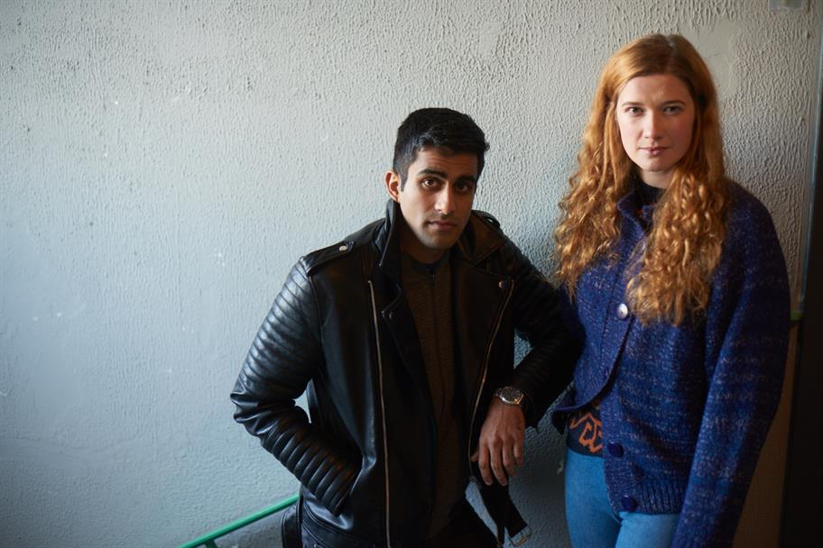 Bally Gill in a black leather jacket and Karen Fishwick in a purple cardigan posing for a photo in a stairwell