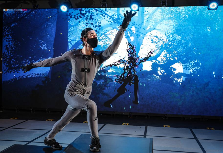 Man in a grey motion capture suit with right arm outstretched behind him and right up up ahead , he is projected on a screen as a collection of branches in human form