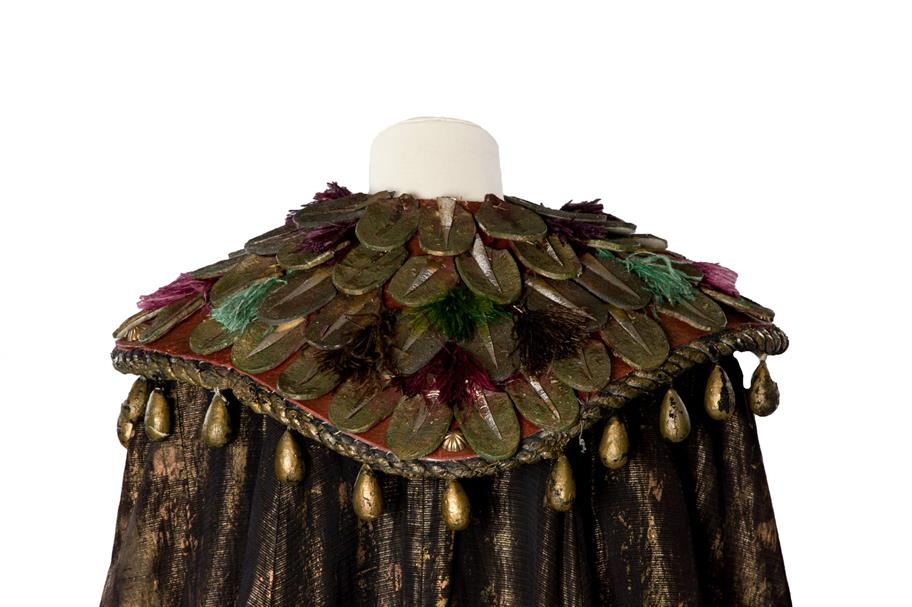 A brown and gold cape with an elaborate collar decorated with fake leaves and feathers