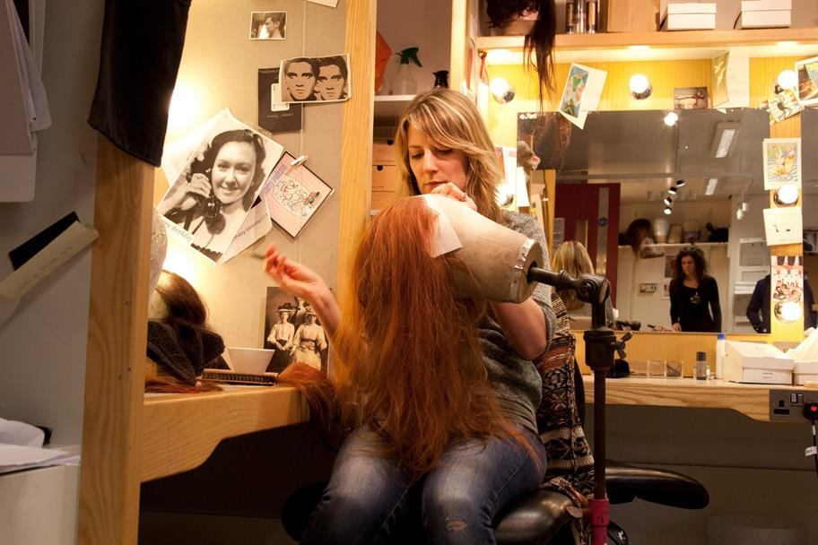 A wig artist stitching a long red wig onto a head model in the dressing room