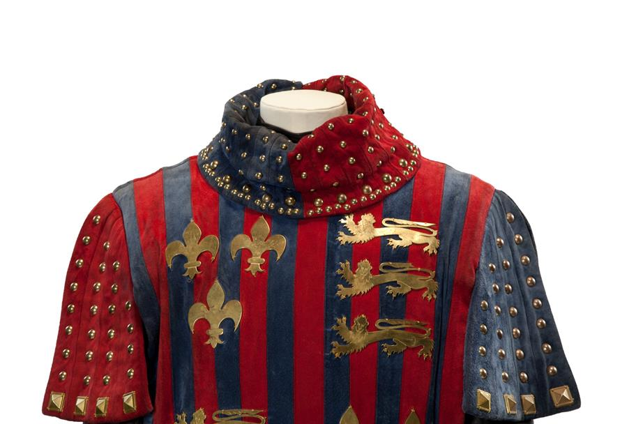 A blue and red robe with golden decorations of lions and fleur de lis