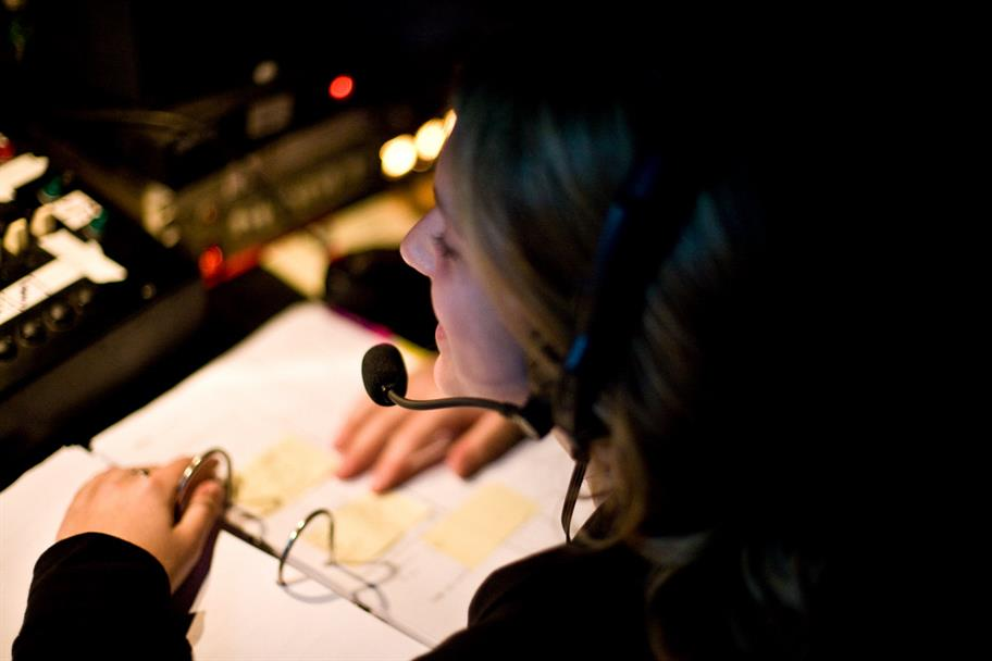 A stage manager wearing a headset and going through a folder of notes