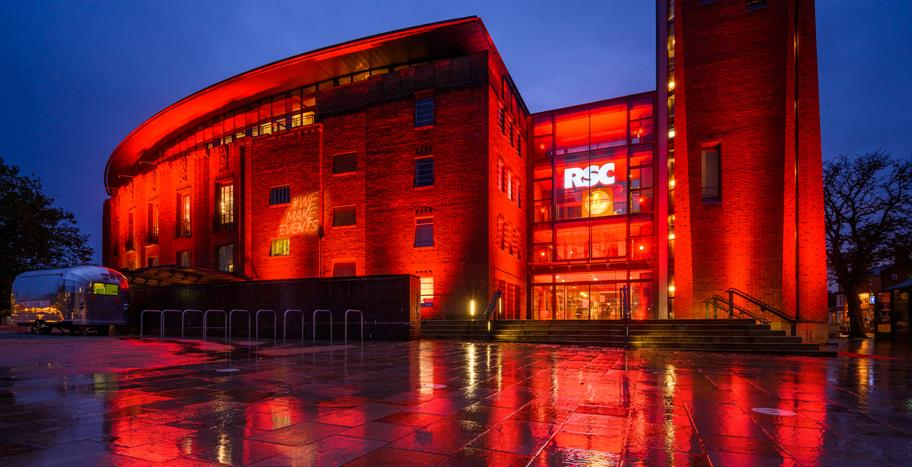outside of the Royal Shakespeare Theatre at night lit dramatically in red