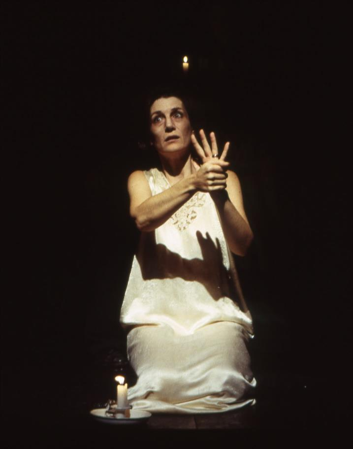 Lady Macbeth kneels on the stage in a white dress her hand help up