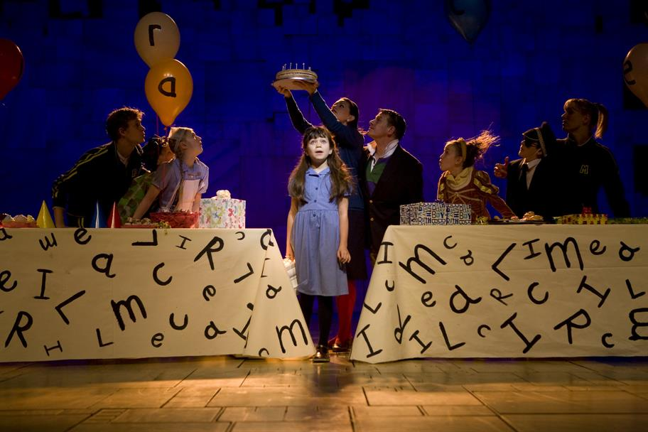 Girl in blue dress stands on stage between 2 long tables covered in letters