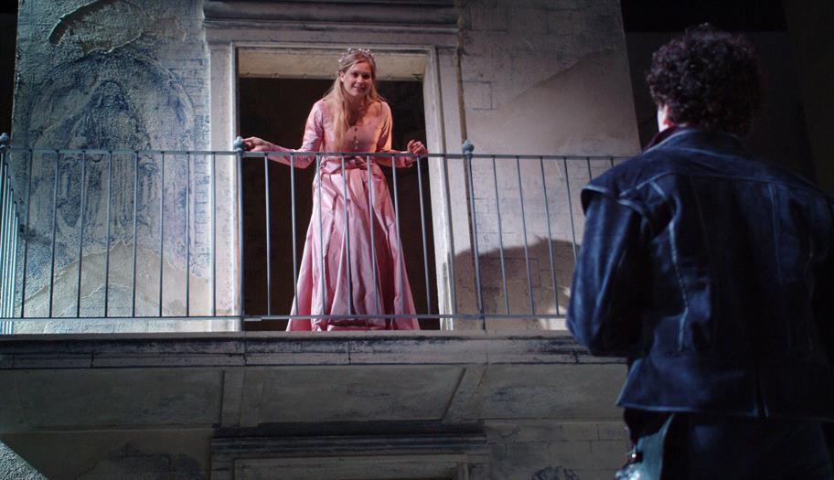 Juliet in a pink dress on a balcony, Romeo below in the shadows