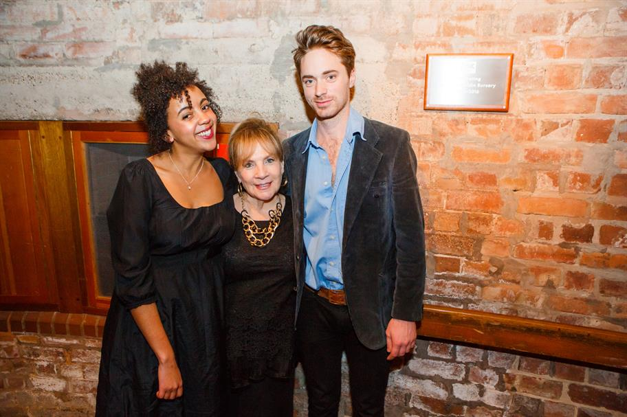 The 2 bursary winners and Brett Goldin's mother next to the plaque int he Swan Theatre