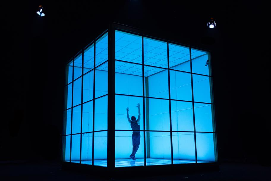 A person stands in a blue-lit transparent box with his hands in the air.