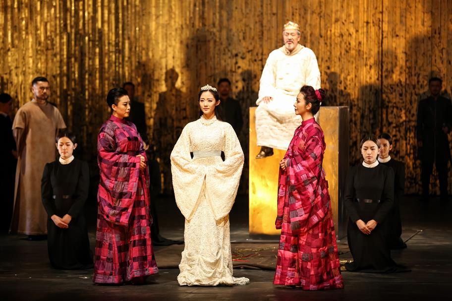 A princess stands in a white dress surrounded by women in red and black. King Lear sits in the background wearing a white gown and golden crown.