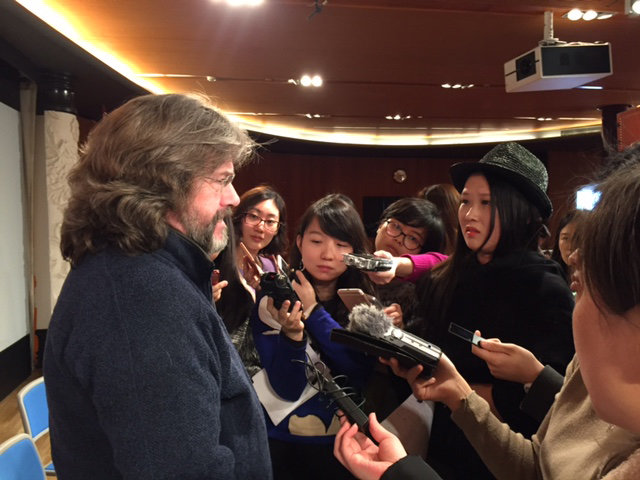 Gregory Doran speaking into several microphones at a press conference in Beijing