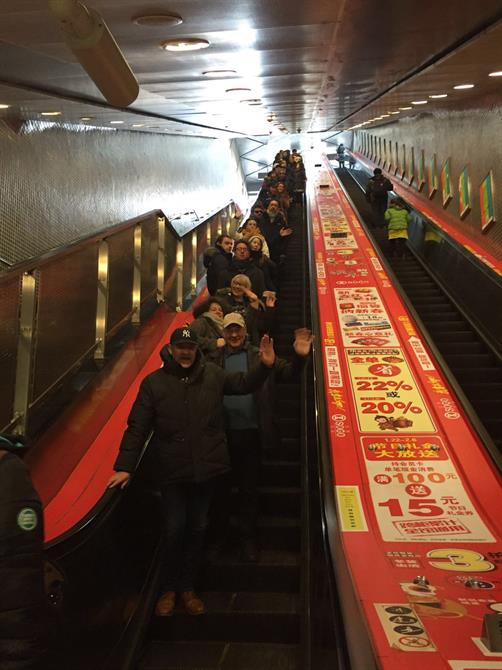 The King and Country Company coming down an escalator and waving in Beijing