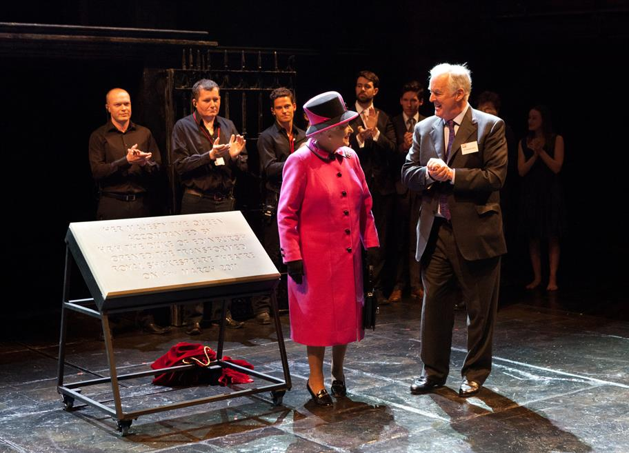 The Queen in a bright pink coat standing on the RST stage talking to Sir Christopher Bland
