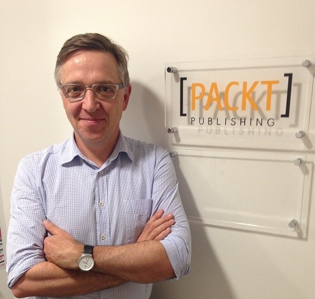 Dave McLean standing, arms folded next to a Packt Publishing sign