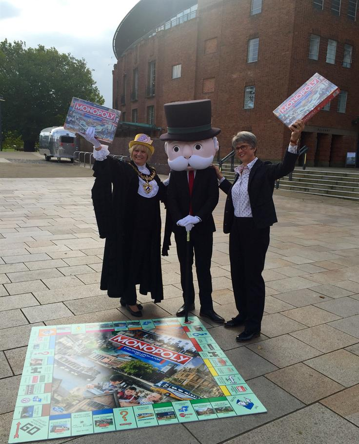 Mr Monopoly in a dark suit with a giant head stands in front of giant Monopoly board flanked by Juliet Short and Catherine Mallyon