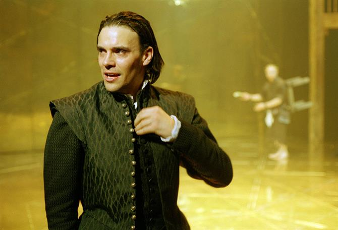 A man in dark Renaissance clothing unbuttoning his vest against a bright yellow stage