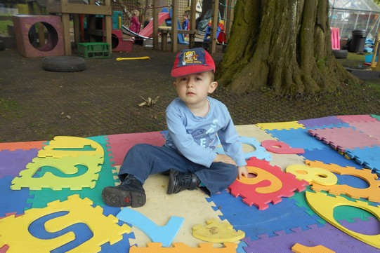a boy sitting on a brightly coloured jigsaw mat outdoors