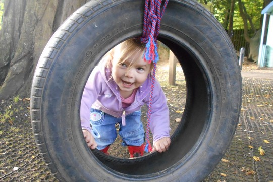 little girl looking through a tyre swing