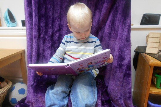 A young child sitting on a purple velvet blanket and reading a large picture book