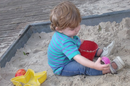 a boy sitting playing in the sandpit