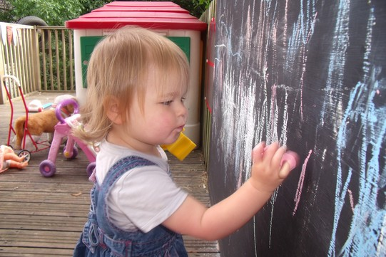 small girl painting a chalkboard outdoors