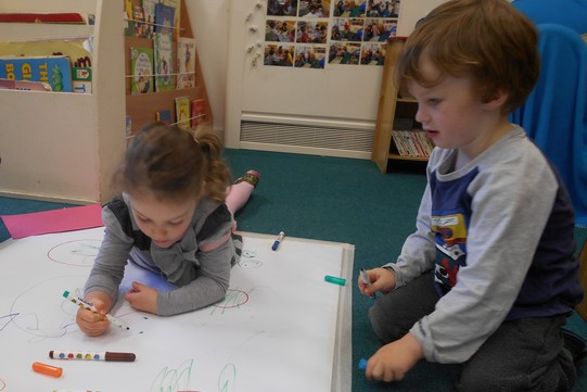 Two children drawing on a large sheet of paper, one lying on the floor, the other kneeling