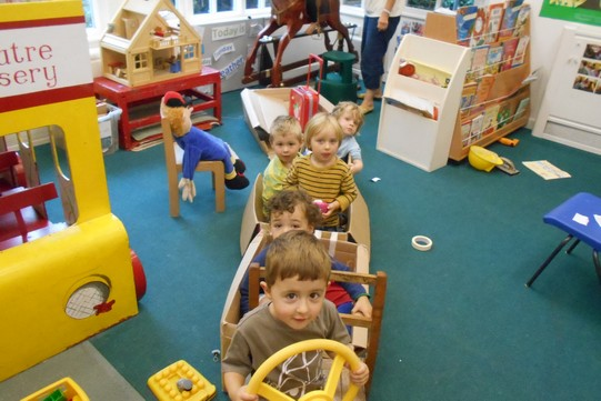 children in the nursery driving a bus made out of cardboard boxes