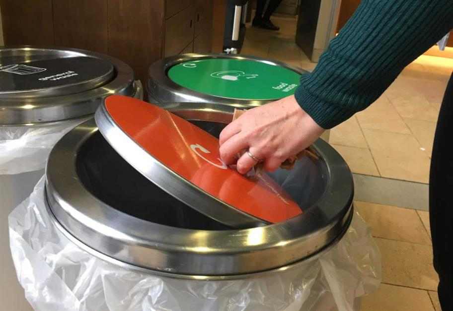 A hand opens the lid of an orange recycling bin.