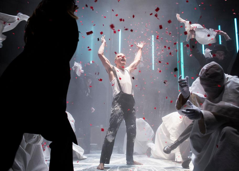 A man on stage throwing his arms in the air surrounded by hooded figures whilst confetti falls down around them