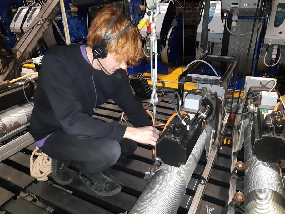 An apprentice in a headset works on a piece of equipment.