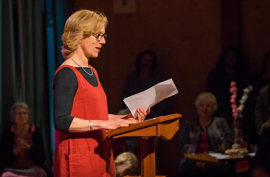 Juliet Stevenson in a red dress over a black top standing at a lectern, speaking