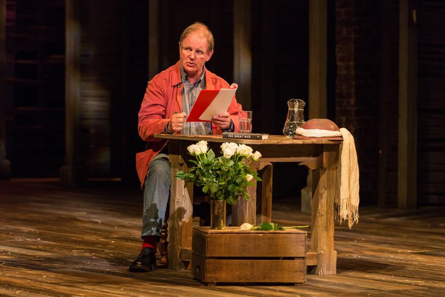 Michael Morpurgo reads from a book on stage.