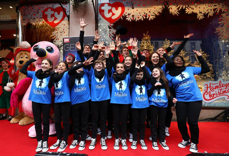 Matilda cast members together with arms raised in front of Hamleys toy store
