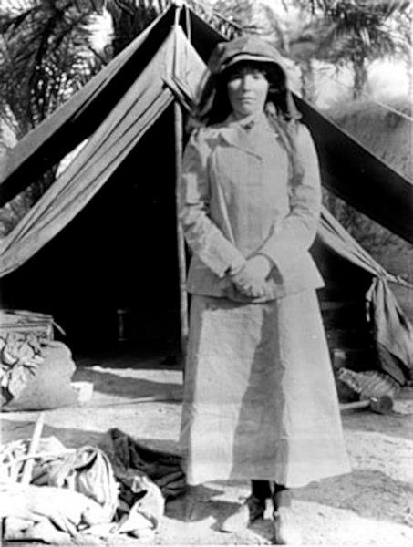 A black and white photo of Gertrude Bell in front of a tent.