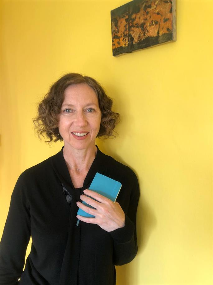Amanda Hadingue dressed in black holding a blue notebook to her chest, standing in front of a bright yellow wall