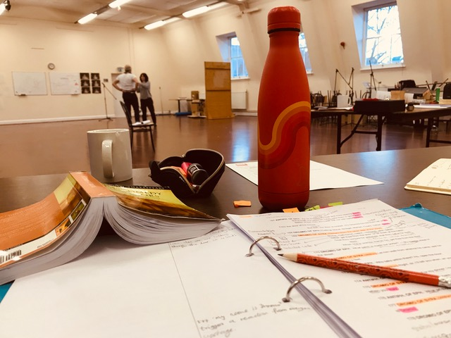 A desk and script in a rehearsal room.